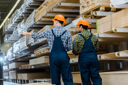 Back view of two multicultural workers in uniform and safety vasts in storehouse