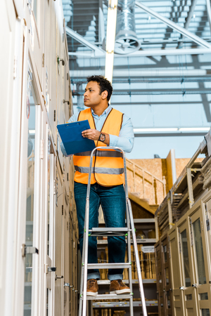 Selective focus of attentive Indian worker in safety vest standing on ladder in warehouse