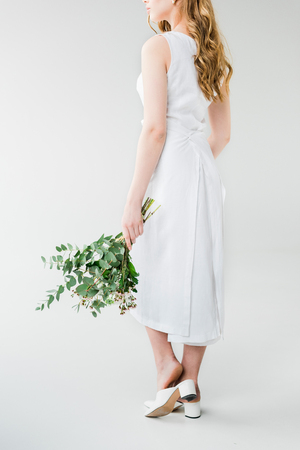 Cropped view of woman in dress holding flowers on white background