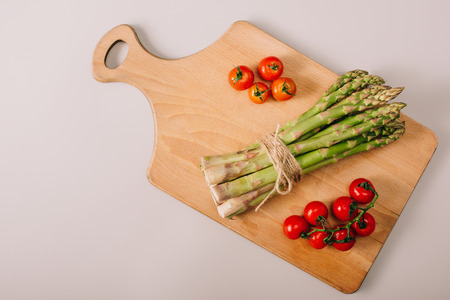 Top view of green uncooked asparagus and cherry tomatoes on wooden cutting board on grey background Standard-Bild - 120875446