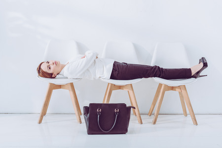 Attractive employee lying on chairs near bag while waiting job interview