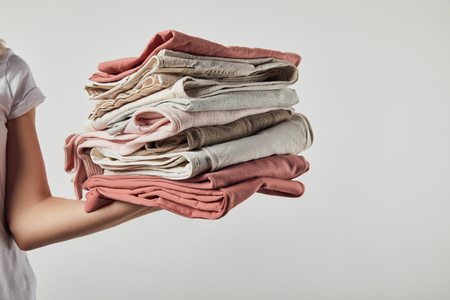 Cropped view of woman holding folded ironed clothes isolated on grey background 版權商用圖片 - 120875429