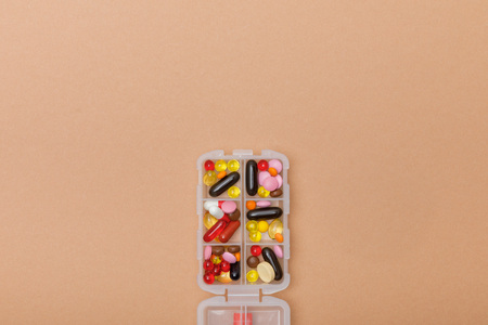 Top view of container with colorful pills on brown surface Imagens - 120875459