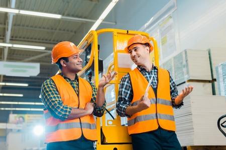 Fröhliche multikulturelle Arbeiter sprechen und gestikulieren, während sie in der Nähe der Scherenhebebühne stehen Standard-Bild