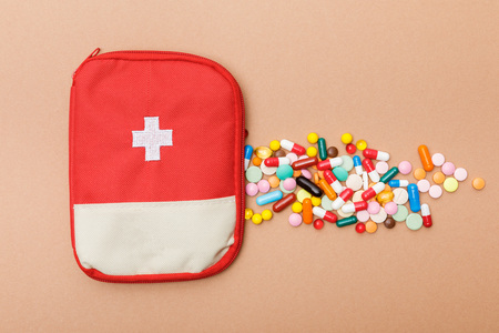 Top view of first aid kit bag and colorful pills on brown surface background Foto de archivo - 120875468