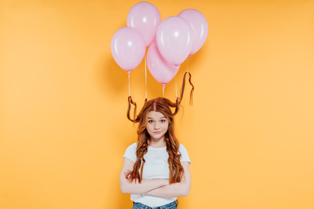Redhead girl with balloons tied to hair looking at camera and posing with crossed arms isolated on yellow background