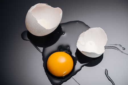 Close up of fresh smashed chicken egg with yolk, protein and eggshell on black background