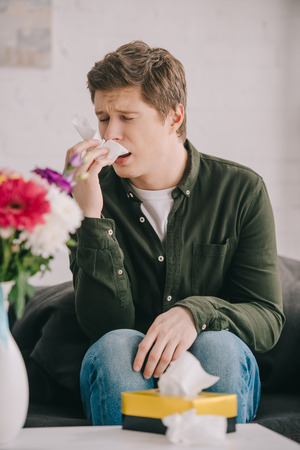 Handsome man with pollen allergy sneezing in tissue near flowers while sitting on sofa