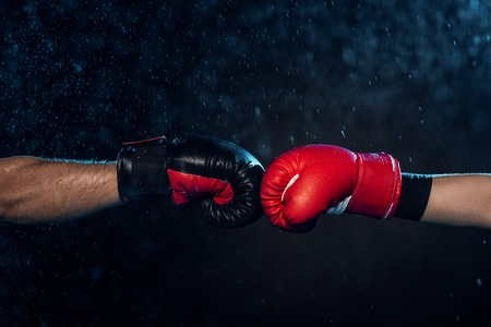 Partial view of two boxers in boxing gloves touching hands on black background