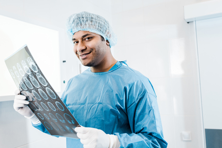 Smiling doctor in uniform and medical cap holding x-ray in and looking at camera Imagens