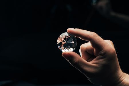 Teilansicht eines Mannes, der einen großen klaren, glänzenden Diamanten auf schwarzem Hintergrund hält holding