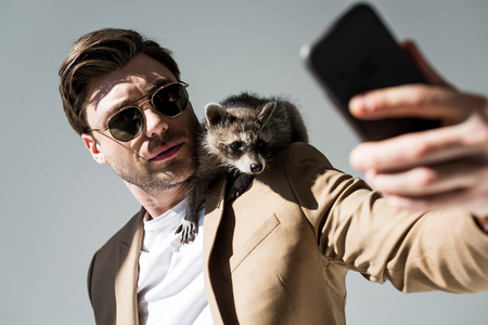 Selective focus of handsome man with adorable raccoon on shoulder, taking selfie with smartphone on grey background
