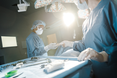 Selective focus of nurse giving medical equipment to surgeon in operating room