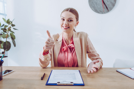 Cheerful recruiter showing thumb up while sitting near clipboard and looking at camera