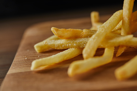 Close up of fresh golden french fries on wooden chopping board