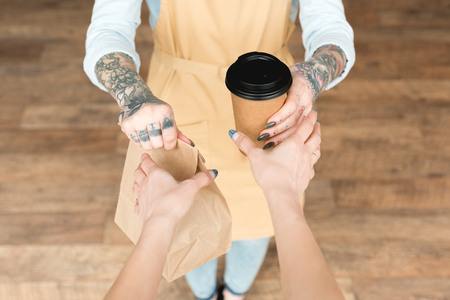Cropped view of tattooed waitress giving paper bag and disposable cup to customer