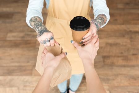 Vista recortada de camarera tatuada dando bolsa de papel y vaso desechable al cliente Foto de archivo
