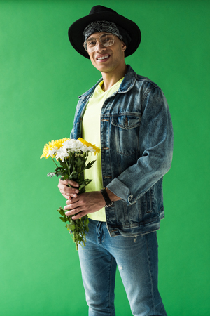 Stylish mixed race man with flowers looking at camera and smiling on green screen background Stock Photo