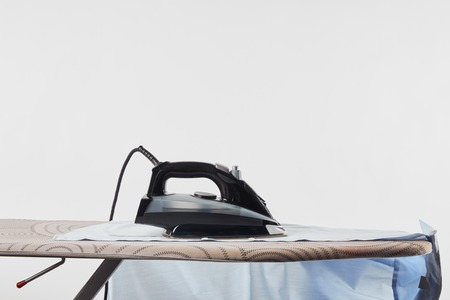 Iron and blue shirt on ironing board isolated on white background 免版税图像