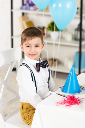 Adorable boy sitting at party table and looking at camera during birthday celebration Standard-Bild