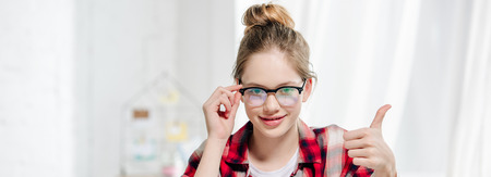 Panoramic shot of teenager in glasses showing thumb up and looking at camera