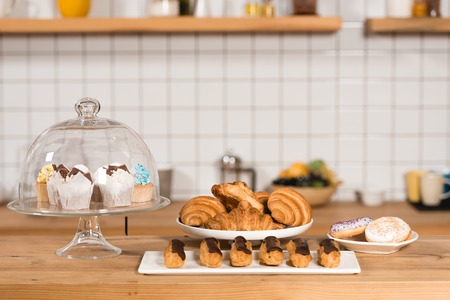 Wooden bar counter with croissants, cakes, eclairs and macaroons in coffee shop
