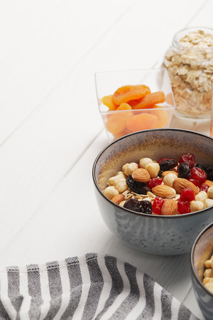 Bowls with muesli, dried berries and nuts served for breakfast with dried apricots on white wooden table with copy space