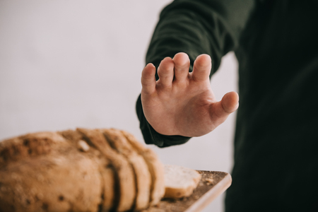 Vista ritagliata dell'uomo che gesticola vicino al tagliere con pane a fette isolato su sfondo grigio