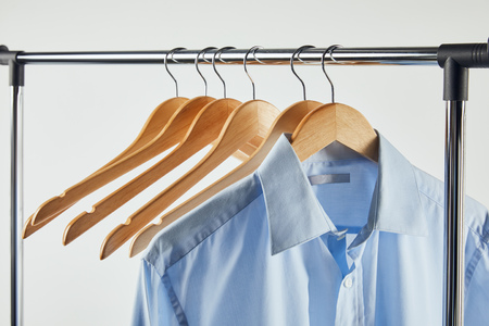 Straight rack, wooden hangers and blue shirt isolated on grey background