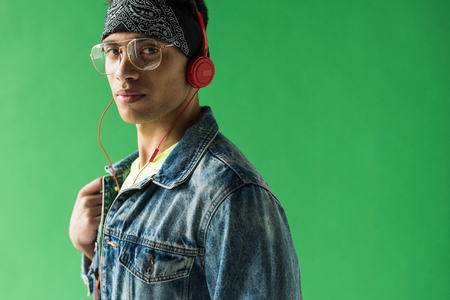 handsome mixed race man in headphones looking at camera while listening music on green screen with copy space