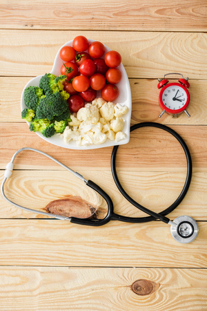 Top view of vegetables on heart-shape plate near stethoscope and retro alarm clock on wooden surface Stock Photo