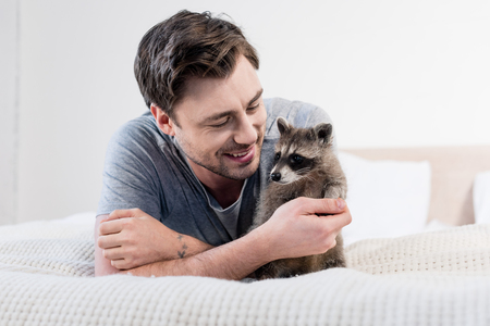 handsome smiling man resting on bedding with adorable raccoon