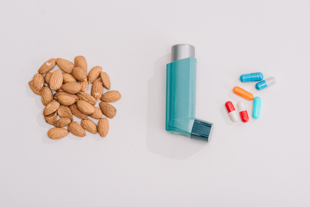 Top view of tasty almonds near pills and blue inhaler on grey background