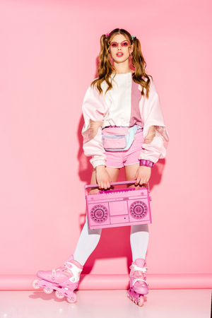Stylish girl in sunglasses holding retro boombox while standing in roller-skates on pink background