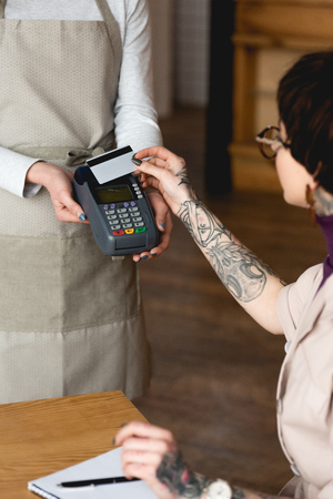 Selective focus of businesswoman holding credit card near waitress with payment terminal Stock Photo - 120875786