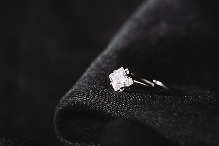 Engagement ring with pure shiny diamond on black cloth