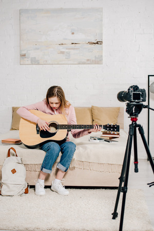 Teenage blogger sitting on bed and playing acoustic guitar in front of camera
