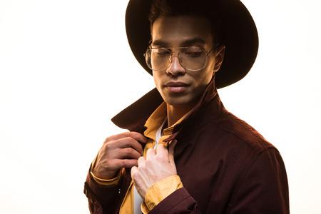 Elegante uomo di razza mista in occhiali e cappello che regola il cappotto e posa isolato su sfondo bianco