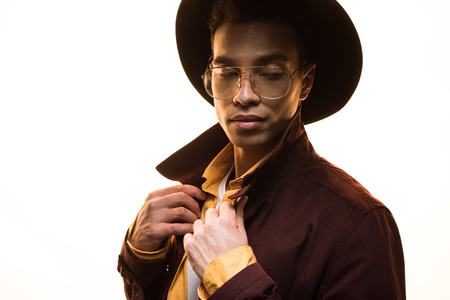 Stylish mixed race man in glasses and hat adjusting coat and posing isolated on white background