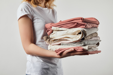 Cropped view of woman holding folded ironed clothes isolated on grey background