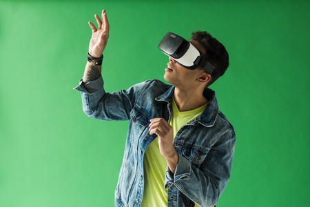 Mixed race man in vr headset gesturing while experiencing virtual reality on green screen background