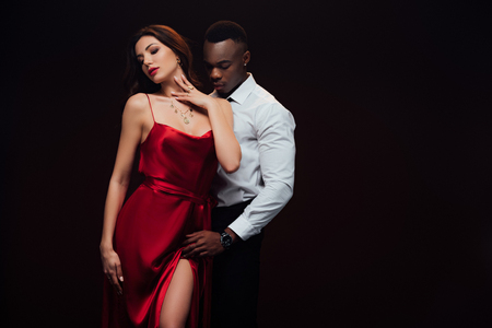Beautiful seductive interracial couple in formal wear posing isolated on black with copy space