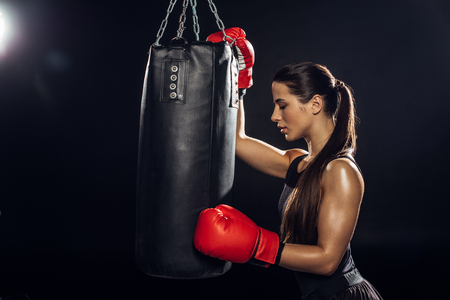 Side view of female boxer in red boxing gloves training with punching bag