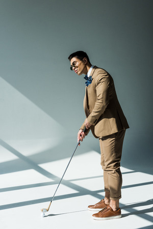 Stylish mixed race man in suit holding golf club on grey with sunlight
