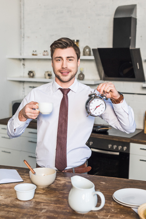 Cheerful man holding coffee cup and alarm clock while standing in kitchen at home Reklamní fotografie