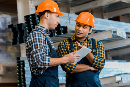 Multicultural, concentrated warehouse workers talking while using digital tablet