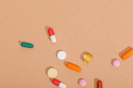 Top view of colorful pills on brown surface Foto de archivo - 120875907