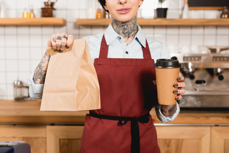 Partial view of barista in apron holding paper bag and disposable cup