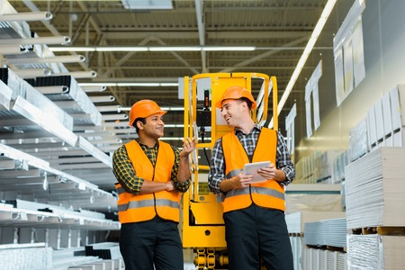 selective focus of cheerful multicultural workers talking while standing near scissor lift 写真素材 - 121415661