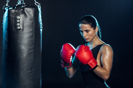Confident boxer in red gloves looking at punching bag on black background